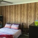 fresh timber wallpaper to cover over an outdated red feature wall